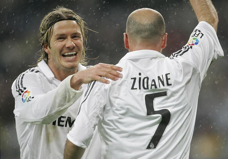 """FILE - This is a Sunday, Jan. 15, 2006 file photo of Real Madrid's David Beckham, left, as he congratulates  goalscorer Zinedine Zidane  during their Spanish league soccer match against Sevilla  at the Santiago Bernabeu Stadium in Madrid, Spain.  David Beckham is retiring from soccer after the season, ending a career in which he become a global superstar since starting his career at Manchester United. The 38-year-old Englishman recently won a league title in a fourth country with Paris Saint-Germain. He said in a statement Thursday May 16, 2013  he is """"thankful to PSG for giving me the opportunity to continue but I feel now is the right time to finish my career, playing at the highest level."""" (AP Photo/Bernat Armangue, File)"""