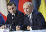 French President Emmanuel Macron and Russian President Vladimir Putin, right, attend a joint news conference with Ukraine's President Volodymyr Zelenskiy and German Chancellor Angela Merkel at the Elysee Palace in Paris, Monday Dec. 9, 2019. Russian President Vladimir Putin and Ukrainian President Volodymyr Zelenskiy met for the first time Monday at a summit in Paris to try to end five years of war between Ukrainian troops and Russian-backed separatists. (Ludovic Marin/Pool via AP)