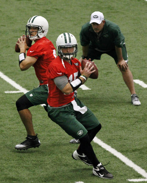 ADVANCE FOR WEEKEND EDITIONS, JULY 21-22 - FILE - In this June 12. 2012, file photo, New York Jets quarterbacks coach Matt Cavanaugh, right, watches as Mark Sanchez, left, and Tim Tebow throw during NFL football practice in Florham Park, N.J. The most popular guy on the Jets' roster isn't even a starter and has no defined role. Tebow is listed as a quarterback _ Sanchez's backup _ but Rex Ryan and the Jets envision as much more.(AP Photo/Mel Evans, File)