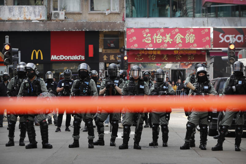 "Riot police watch as protesters march during a demonstration against ""parallel traders"" who buy goods in Hong Kong to resell in mainland China in Sheung Shui, near the Chinese border in Hong Kong, Sunday, Jan. 5, 2020. Protesters in Hong Kong marched through the border town Sunday to oppose traders from mainland China. (AP Photo/Andy Wong)"