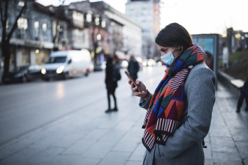 Side view of young woman with face mask on the street, waiting for city transport and looking down at her smartphone.