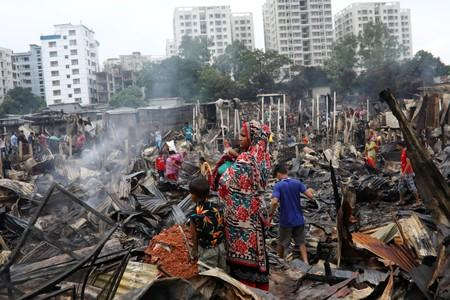 Slum dwellers are seen gather near their shelters after fire burnt them out in Dhaka