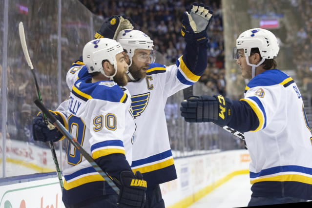 St. Louis Blues defenseman Alex Pietrangelo (27) celebrates with center Ryan O'Reilly (90) and left wing Sammy Blais (9) after scoring against the Toronto Maple Leafs during third-period NHL hockey game action in Toronto, Monday, Oct. 7, 2019. (Chris Young/The Canadian Press via AP)