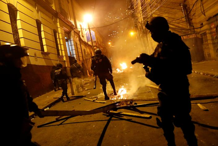 A police officer stamps on a fire during clashes between protesters against Bolivia's President Evo Morales and government supporters, in La Paz, Bolivia Nov. 7, 2019. (Photo: Kai Pfaffenbach/Reuters)