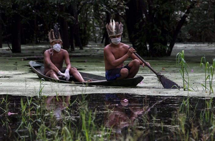 """<span class=""""caption"""">Satere-mawe Indigenous men in face masks paddle the Ariau River in hard-hit Manaus state during the coronavirus pandemic, May 5, 2020. </span> <span class=""""attribution""""><a class=""""link rapid-noclick-resp"""" href=""""https://www.gettyimages.com/detail/news-photo/satere-mawe-indigenous-men-navigate-the-ariau-river-during-news-photo/1211905066?adppopup=true"""" rel=""""nofollow noopener"""" target=""""_blank"""" data-ylk=""""slk:Ricardo Oliveira /AFP via Getty Images"""">Ricardo Oliveira /AFP via Getty Images</a></span>"""
