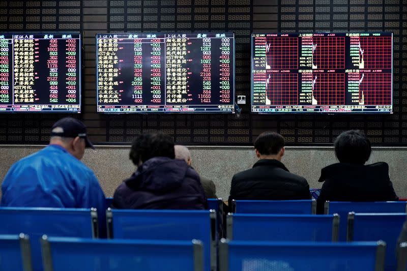 Investors look at screens showing stock information at a brokerage house in Shanghai