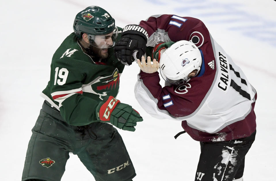 Minnesota Wild center Luke Kunin (19) and Colorado Avalanche left wing Matt Calvert (11) fight during the third period of an NHL hockey game Sunday, Feb. 9, 2020, in St. Paul, Minn. Both players received penalties. The Avalanche won 3-2. (AP Photo/Hannah Foslien)