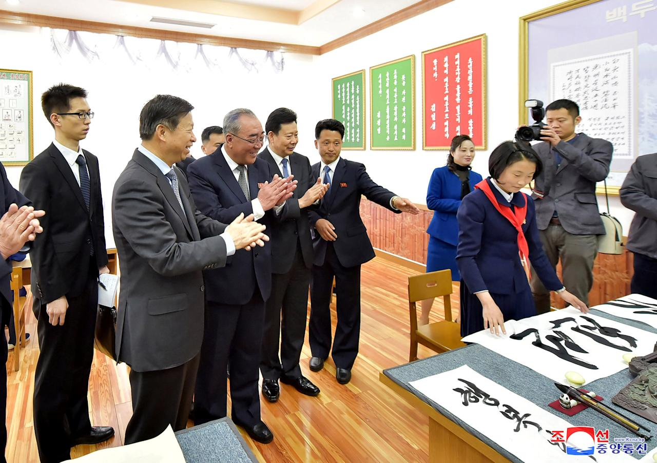 Song Tao (2nd L), head of China's Communist Party international liaison department, looks at calligraphy as he tours a school in this undated photo released by North Korea's Korean Central News Agency (KCNA) in Pyongyang on April 18, 2018. KCNA/via Reuters  ATTENTION EDITORS - THIS IMAGE WAS PROVIDED BY A THIRD PARTY. REUTERS IS UNABLE TO INDEPENDENTLY VERIFY THIS IMAGE. NO THIRD PARTY SALES. SOUTH KOREA OUT. NO COMMERCIAL OR EDITORIAL SALES IN SOUTH KOREA.
