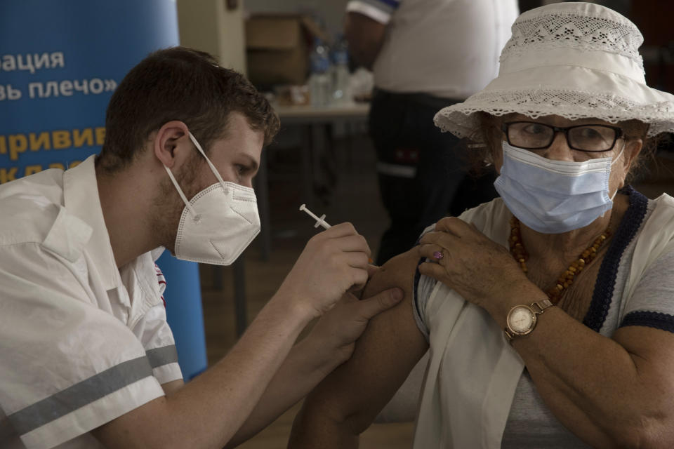 An Israeli woman receives a third coronavirus vaccine injection at a senior center in Jerusalem, Wednesday, Aug. 4, 2021. Israeli health authorities began administering coronavirus booster shots last week to people over 60 who've already received both does of a vaccine, in a bid to combat a recent spike in cases. (AP Photo/Maya Alleruzzo)