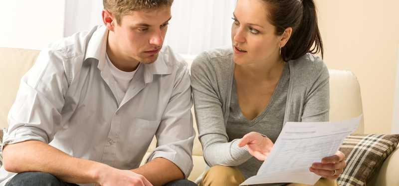 A young couple reviews paperwork while sitting on a couch.
