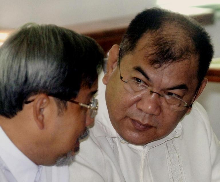 Major General Carlos Garcia (right) talks to his lawyer at a court in Manila on December 2, 2005