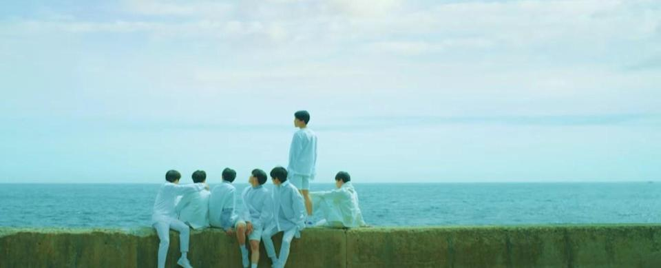 BTS all wear white and sit on a concrete wall by the ocean in the Euphoria music video