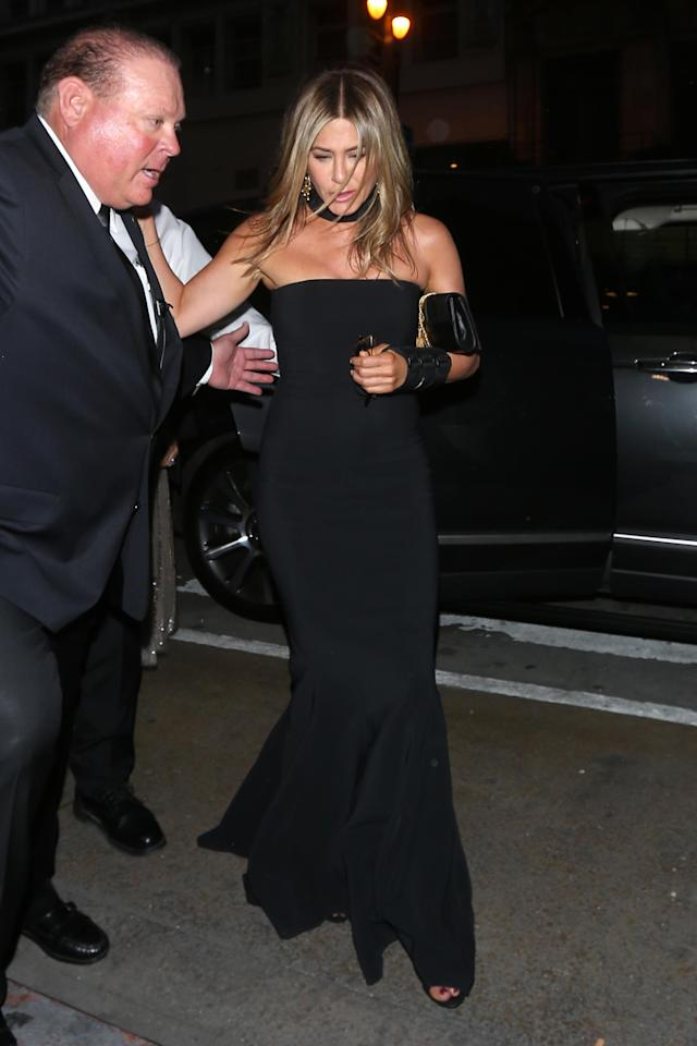 Jennifer Aniston arriving for Gwyneth Paltrow and Brad Falchuk's engagement party on April 14. The actress appeared to have a wrist injury and attended with her pal Amanda Anka, wife of Jason Bateman. (Photo: Splash News)