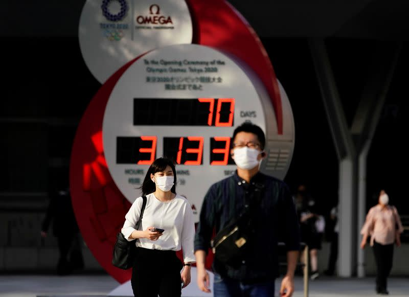 Passersby wearing protective face masks walk near a countdown clock of Tokyo 2020 Olympic Games