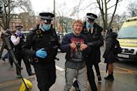 A protester is removed, by police officers, from the encampment in Euston Square Gardens in central London, where HS2 Rebellion protesters have built a 100ft tunnel network, which they are ready to occupy, after claiming the garden is at risk from the HS2 line development. Picture date: Wednesday January 27, 2021.