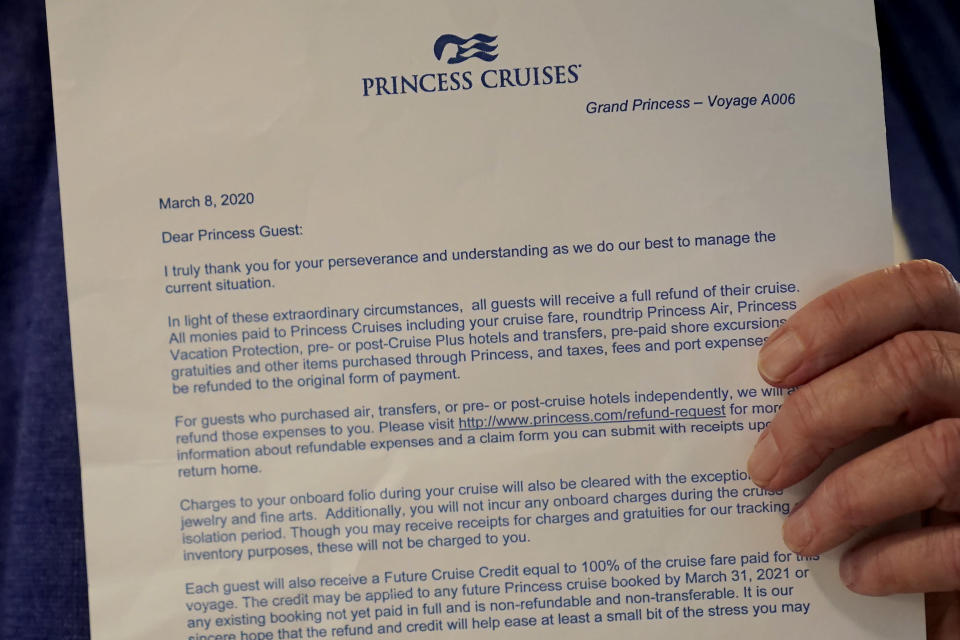 Laurie Miller shows a letter from Princess Cruises while interviewed in San Jose, Calif., Wednesday, March 10, 2021. Miller and her husband were passengers on the Grand Princess cruise ship, which had captured the world's attention in 2020 when it became clear the coronavirus pandemic had arrived at U.S. shores on board the boat. (AP Photo/Jeff Chiu)