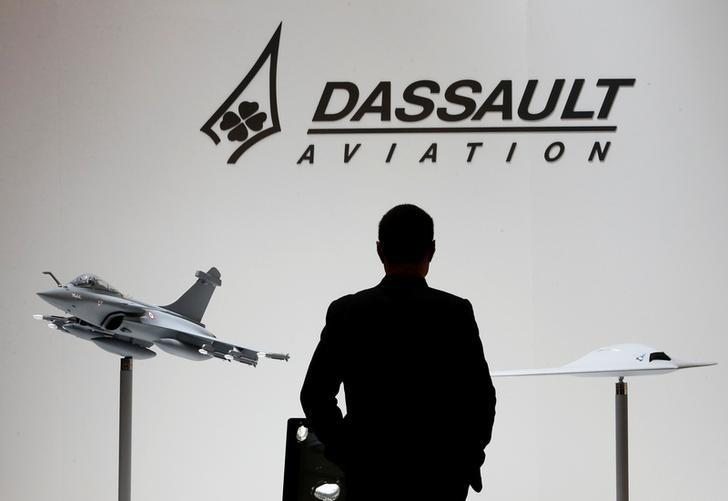 A visitor looks at replicas of the fighter jet Rafale (L) and Neuron on the Dassault booth during the European Business Aviation Convention & Exhibition (EBACE) at Cointrin airport in Geneva, Switzerland, in this picture taken on May 19, 2015. REUTERS/Denis Balibouse/File Photo
