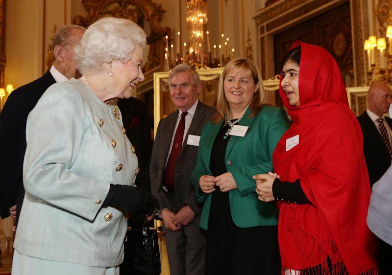 Britain's Queen Elizabeth II meets Malala Yousafzai during a reception for youth, education and the Commonwealth at Buckingham Palace, London, Friday Oct. 18, 2013. The Pakistani teenager, an advocate for education for girls, survived a Taliban assassination attempt last year on her way home from school. (AP Photo/Yui Mok, Pool)