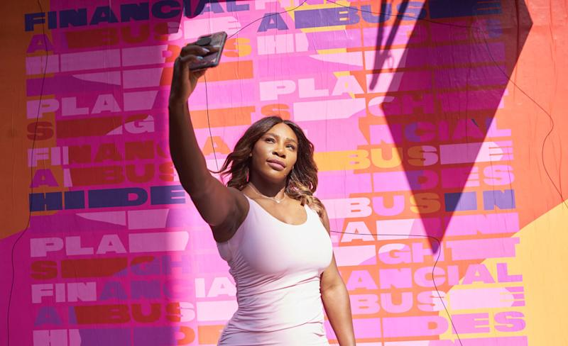 Serena Williams in front of the mural designed by artist Isabel Castillo Guijarro for Allstate Purple Purse Foundation. (Photo: Courtesy of Allstate Foundation Purple Purse)