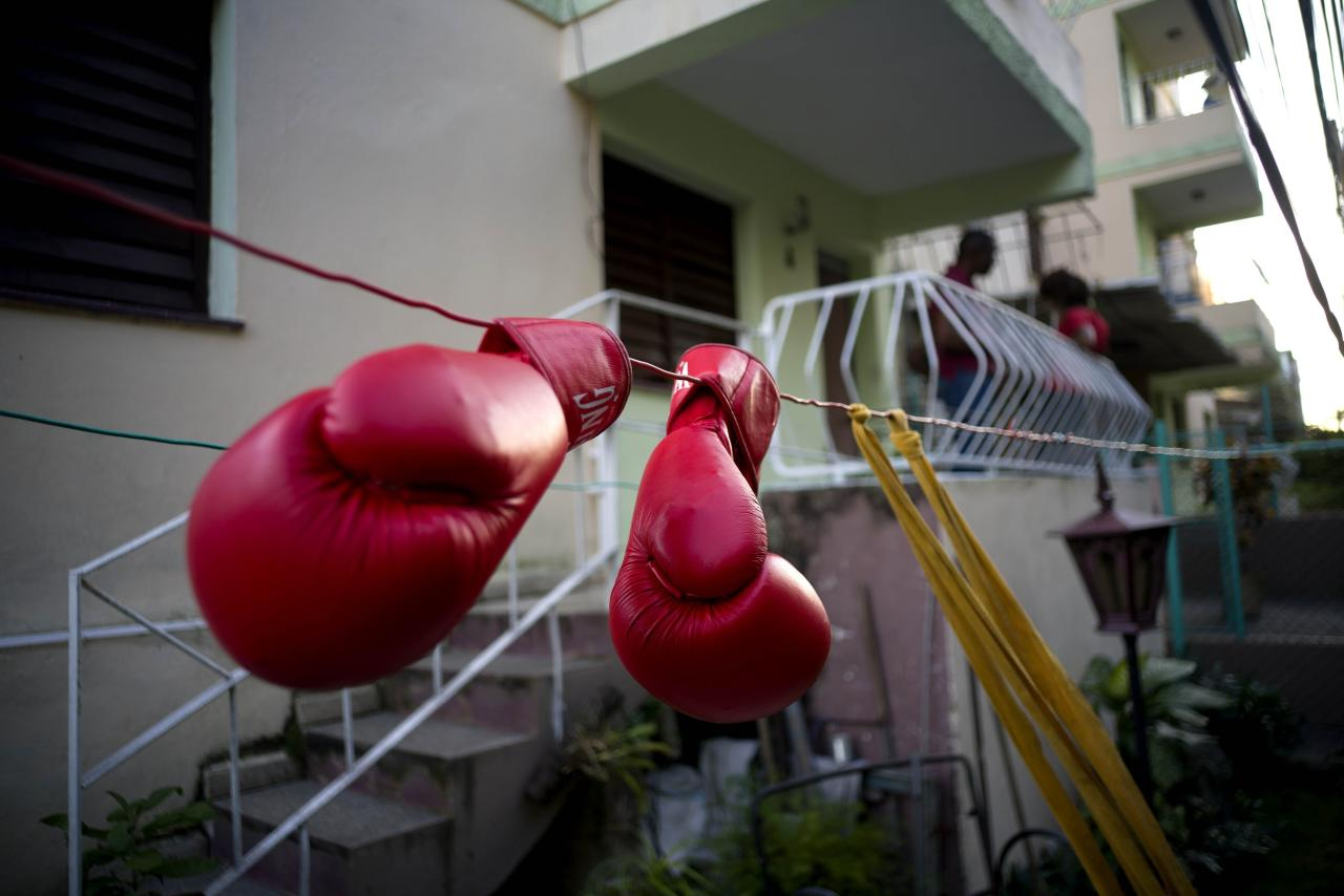 In this Jan. 19, 2017 photo, Idamelys Moreno's boxing gloves hang on a line to dry, after a training session in Havana, Cuba. Women were first allowed to box at the Olympics during the 2012 Summer Olympics but they are still not allowed to box in Cuba. (AP Photo/Ramon Espinosa)
