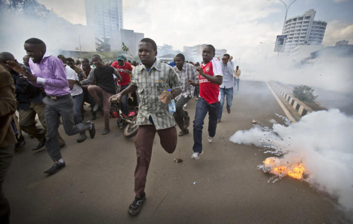 Opposition supporters, some carrying rocks, flee from exploding tear gas grenades fired by riot police, during a protest in downtown Nairobi, Kenya, May 16, 2016. Kenyan police have tear-gassed and beaten opposition supporters during a protest demanding the disbandment of the electoral authority over alleged bias and corruption. (AP Photo/Ben Curtis)