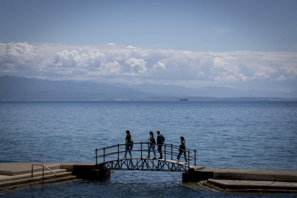 A group of tourists walk across a bridge on the seafront in Opatija, Croatia, Saturday, May 15, 2021. Croatia has opened its stunning Adriatic coastline for foreign tourists after a year of depressing coronavirus lockdowns and restrictions. (AP Photo/Darko Bandic)