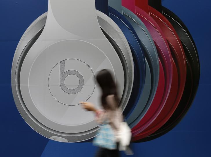 A woman holding her mobile phone walks past an advertisement for beats brand headphones outside an electronic store in Tokyo