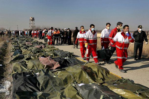 PHOTO: Rescue workers carry the body of a victim of a Ukrainian plane crash in Shahedshahr, southwest of the capital Tehran, Iran, Jan. 8, 2020. (Ebrahim Noroozi/AP)