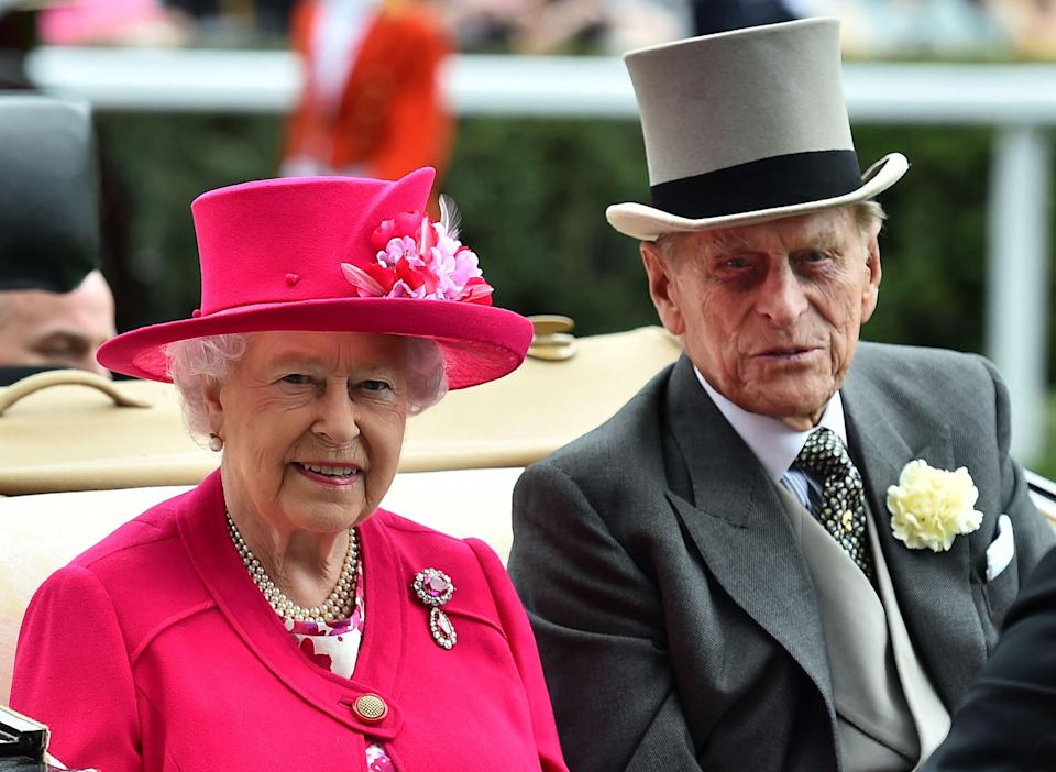 In this file photo taken on 16 June 2015, the Queen and Prince Philip arrive by horse-drawn carriage on the first day of the annual Royal Ascot horse racing event near Windsor, Berkshire (AFP via Getty Images)