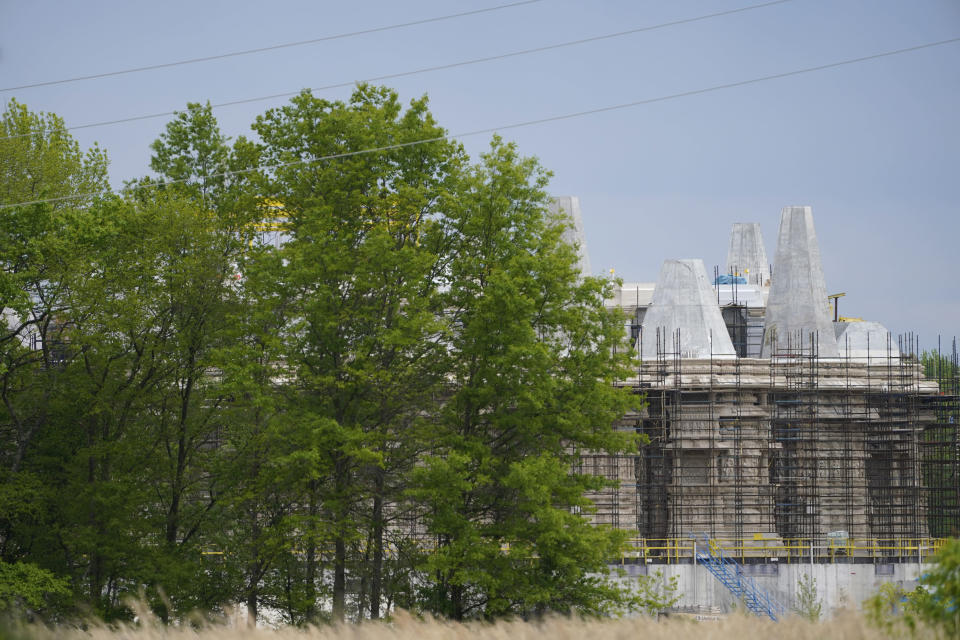 A part of the BAPS Shri Swaminarayan Mandir is covered in scaffolding in Robbinsville Township, N.J., Tuesday, May 11, 2021. A lawsuit claims workers from marginalized communities in India were lured to New Jersey and forced to work more than 12 hours per day at slave wages to help build a Hindu temple. (AP Photo/Seth Wenig)