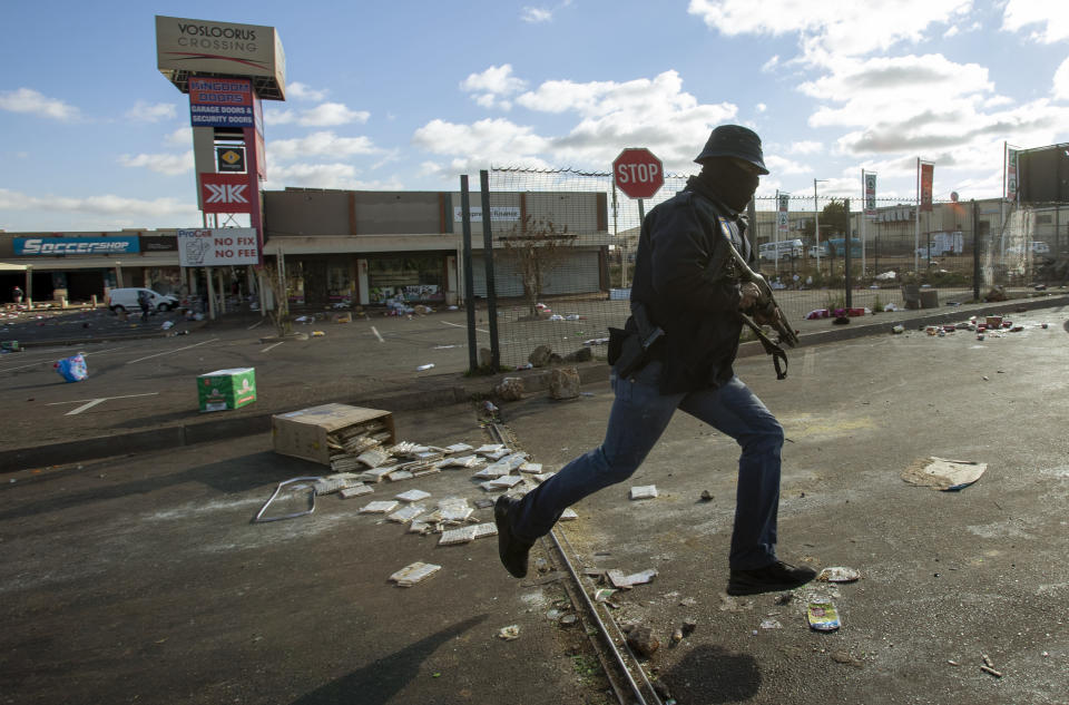 A plainclothes officer pursues looters at a shopping center in the Soweto township of Johannesburg, South Africa, on Tuesday July 13, 2021. Rioting in the country continued as police and the military struggle to quell the violence in Gauteng and KwaZulu-Natal provinces. The violence started in various parts of KwaZulu-Natal last week when former President Jacob Zuma began serving a 15-month sentence for contempt of court. (AP Photo/Themba Hadebe)