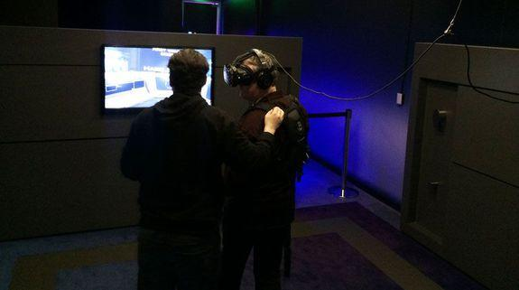 "An IMAX VR employee sets up a new user in one of their VR ""pods."""