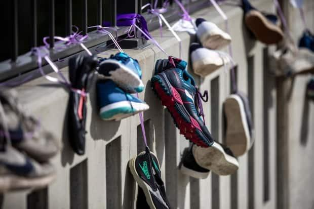 Shoes representing a life lost to a drug overdose hang in Vancouver on International Overdose Awareness Day.  (Ben Nelms/CBC - image credit)