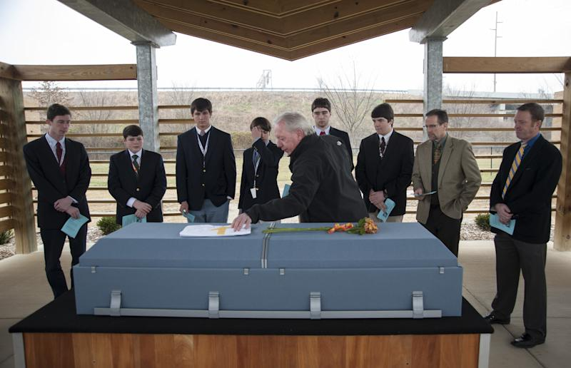 Buddy Dumeyera, the Louisville deputy coroner who runs the indigent burial program, places a flag on 48-year-old Francisco Carmona's casket as students from the St. Joseph of Arimathea Society at Trinity High School prepare to perform their duties Wednesday, Feb. 6, 2013 at Meadow View Cemetery in Louisville, Ky. The students are, from left, Paul Adams, 18, senior, Jeremy Gaines, 16, junior, Nolan Riley, 14, freshman, Greg Atchison, 17, senior, Sean Dageforde, 17, Jake Eddy, 18, senior, school principal Dan Zoeller and social studies teacher Chad Waggoner.  Counties across Kentucky, like much of the country, are seeing more cases of unclaimed bodies and families who can't afford to bury or cremate a loved one. Every situation is unique, but coroners and local government officials tell a similar story: The economic downturn has left many people without the money to pay for funeral services that can cost thousands of dollars, and it's falling on cities and states to cover the bills.  (AP Photo/Brian Bohannon)