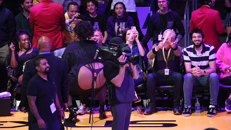 A photo of Lizzo wearing a black dress with a cutout that exposes her thong at a basketball game between the Los Angeles Lakers and the Minnesota Timberwolves at Staples Center on December 08, 2019 in Los Angeles, California