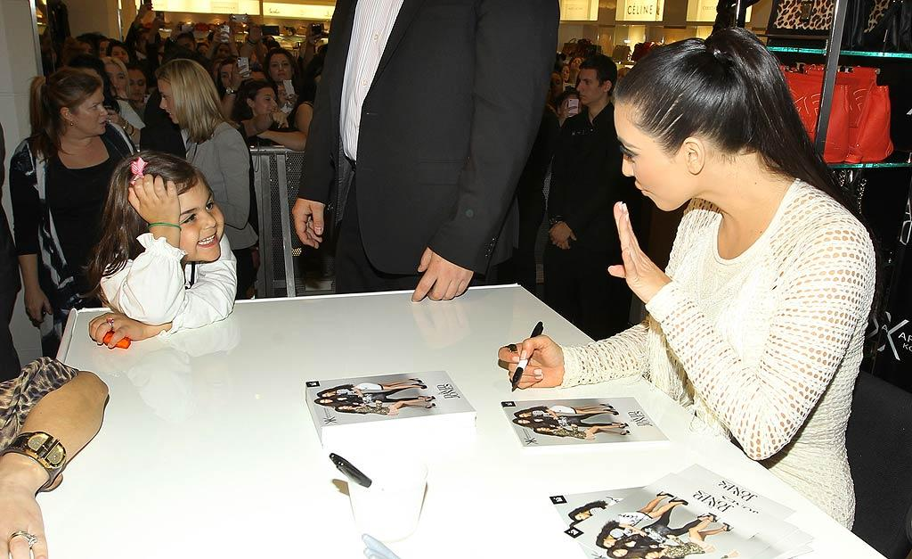 Later, Kim made an appearance at a department store in downtown Sydney. While the reality star has has understandably not been in a very good mood over the past few days, her adorable little fan managed to put a smile on her face. (11/3/2011)