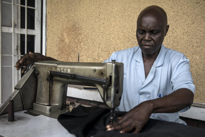 Thomas Disolo sews a tsetse fly trap at the Ministry of Health. (Neil Brandvold/DNDi)