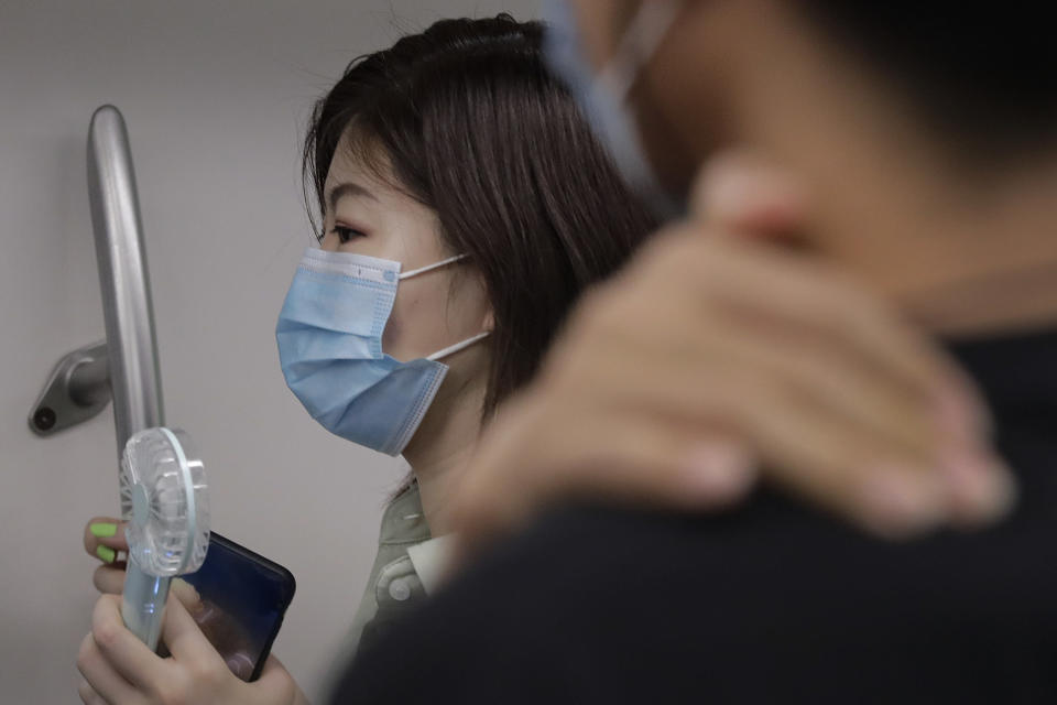 A woman wearing a face mask to protect against the new coronavirus uses an electric fan to cool herself as she rides in a subway train in Beijing, Wednesday, July 29, 2020. China reported more than 100 new cases of COVID-19 on Wednesday as the country continues to battle an outbreak in Xinjiang. (AP Photo/Andy Wong)