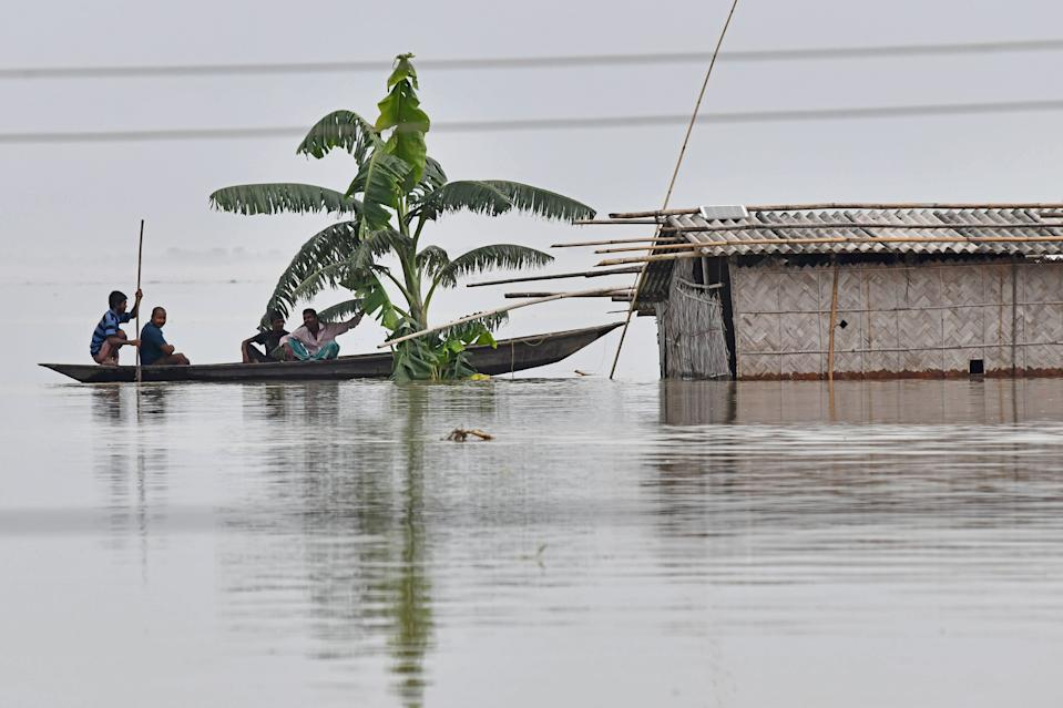 Villagers paddle their boat next to a partially submerged hut in the flood affected area of Hatishila, in Kamrup district of Assam state on July 14, 2020. Flooding is an annual phenomenon in India's northeast, claiming hundreds of lives each year. (Photo by BIJU BORO/AFP via Getty Images)