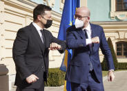 In this handout photo provided by the Ukrainian Presidential Press Office, Ukrainian President Volodymyr Zelenskiy, left, and European Council President Charles Michel bump elbows as they meet in Kyiv, Ukraine, Wednesday, March 3, 2021. (Ukrainian Presidential Press Office via AP)