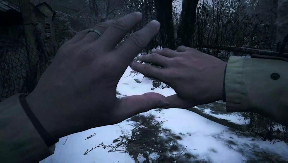 Screen view of two hands stretched out over a snowy landscape.