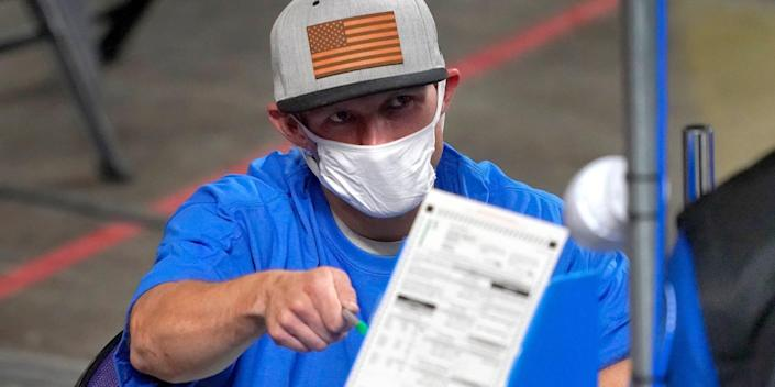 In this May 6, 2021 file photo, Maricopa County ballots cast in the 2020 general election are examined and recounted by contractors working for Florida-based company, Cyber Ninjas at Veterans Memorial Coliseum in Phoenix.