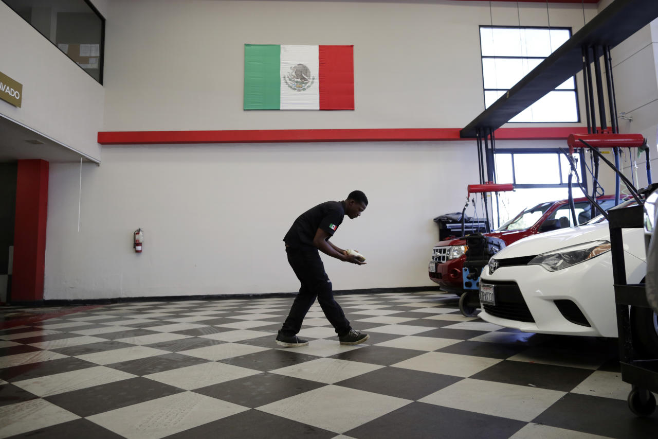 In this May 24, 2017 photo, Jeff Theodull, of Haiti, works at a luxury car wash in Tijuana, Mexico. The Mexican government is giving Haitians one-year, renewable visas that allow them to work but not bring family. Rodulfo Figueroa, the region's top immigration official, says Mexico is practicing what it asks of the U.S. and other countries. (AP Photo/Gregory Bull)