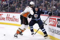 Winnipeg Jets' Jack Roslovic (28) braces for the hit as Anaheim Ducks' Erik Gudbranson (6) checks him into the boards during the second period of an NHL hockey game, Sunday, Dec. 8, 2019 in Winnipeg, Manitoba. (Fred Greenslade/The Canadian Press via AP)