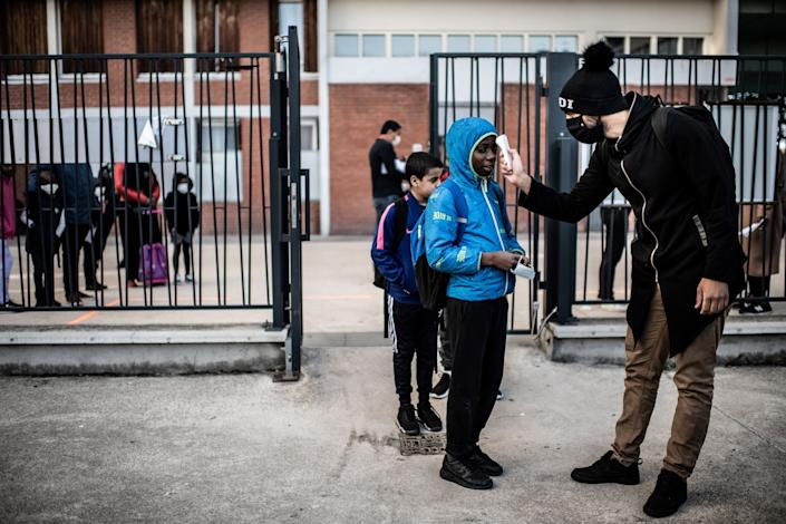 Students have their temperatures checked before entering the Saint-Exupery school in the Paris' suburb of La Courneuve on May 14. (Photo: MARTIN BUREAU via Getty Images)