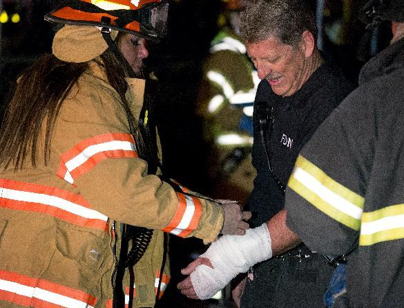 An FDNY firefighter is treated for an arm injury at the scene of the rescue of a trapped worker at an MTA subway construction project in New York Tuesday, March 19, 2013. The worker was rescued early Wednesday morning after being trapped up to his chest in debris for several hours. (AP Photo/Craig Ruttle)
