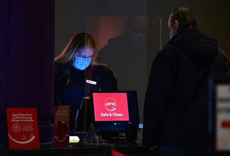An employee helps a moviegoer with a ticket purchase at AMC Empire 25 off Times Square as New York City's cinemas reopen on March 5, 2021