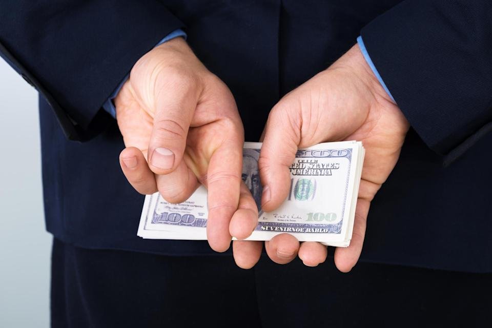 A businessman in a suit hiding a stack of hundred dollar bills behind his back, with his fingers crossed.