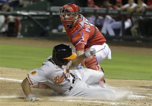 Baltimore Orioles' Henry Urrutia, left, is tagged out by Texas Rangers catcher A.J. Pierzynski at home plate during the third inning of a baseball game Saturday, July 20, 2013, in Arlington, Texas. Urrutia was trying to score from third base on a fly ball by Nate McLouth. (AP Photo/LM Otero)