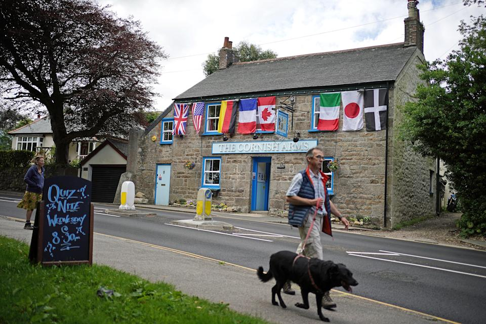 World flags, including the flag of Cornwall (right), decorate The Cornish Arms in St Ives, Cornwall (PA)